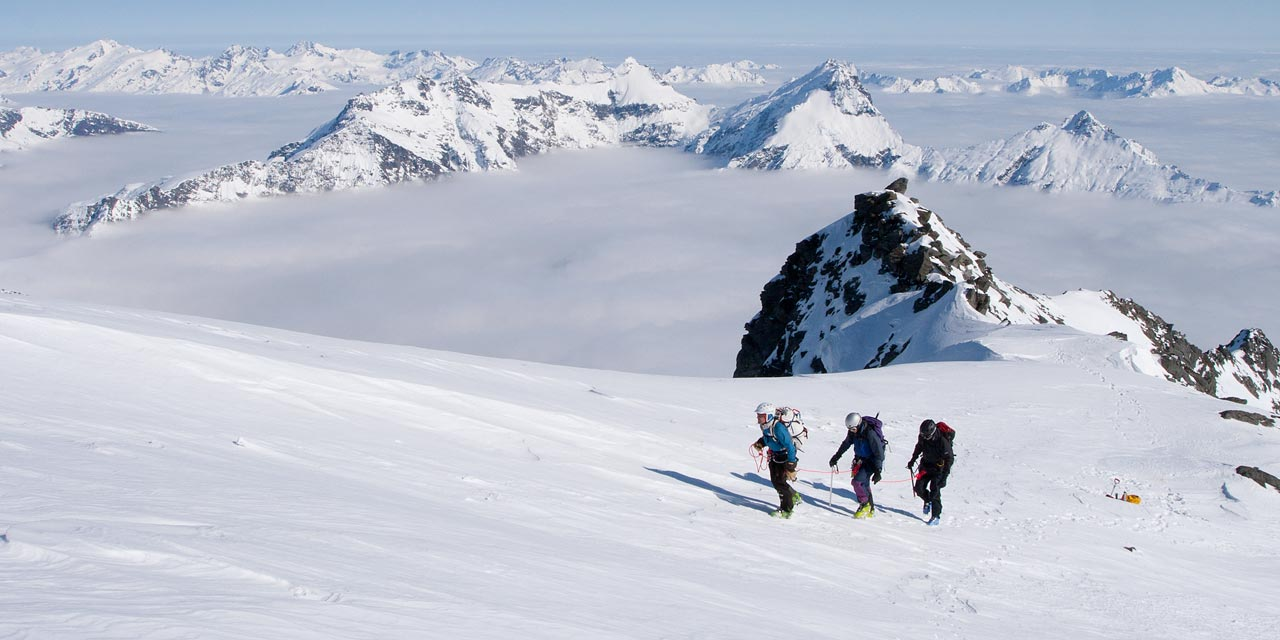 Climbers ascending the upper snow slopes of Mt. Aspiring