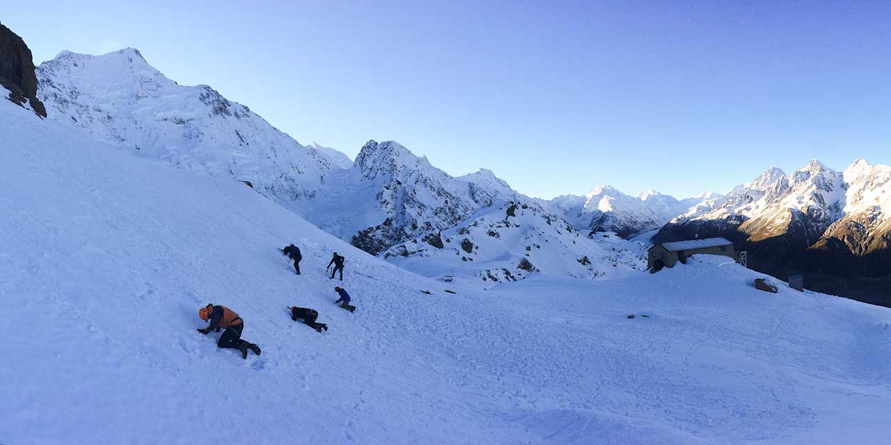 Snow anchors instruction in front of Mount Cook and Caroline Hut