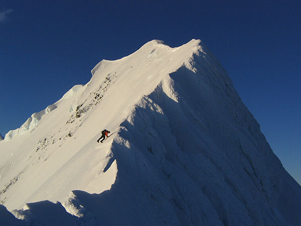 A guide climbs the final steep rise to the summit.