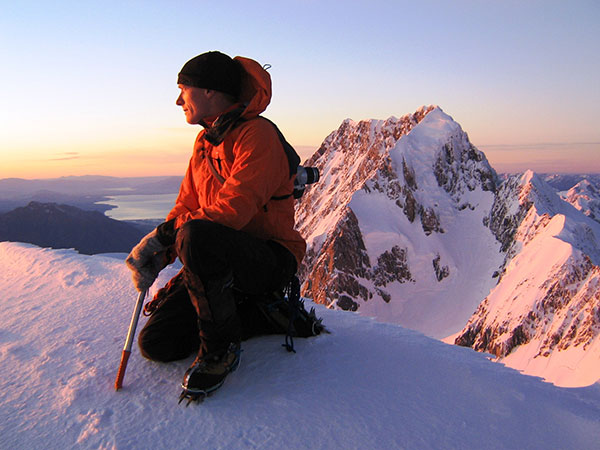 A climber admires the view near the summit of Mt Tasman, Mt Cook in the background.