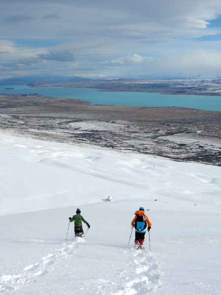 Snowshoers returning to Rex Simpson Hut, Lake Tekapo behind.